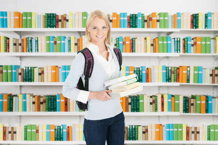 Portrait of smiling female university student holding file while standing at library photo