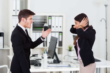 standing businessman: Side view of boss yelling at secretary covering ears in office Stock Photo