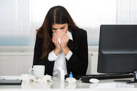 woman work: Sick young businesswoman blowing her nose at computer desk in office Stock Photo