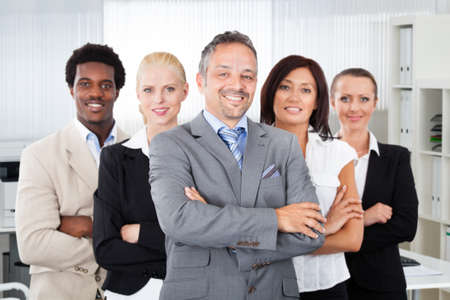 happy work: Portrait of confident manager standing arms crossed with multiethnic team in office