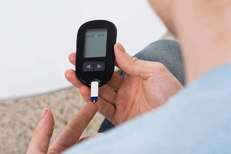 personas saludables: Vista de ángulo alto del hombre de mediana edad azúcar en la sangre comprobar con medidor de glucosa en casa