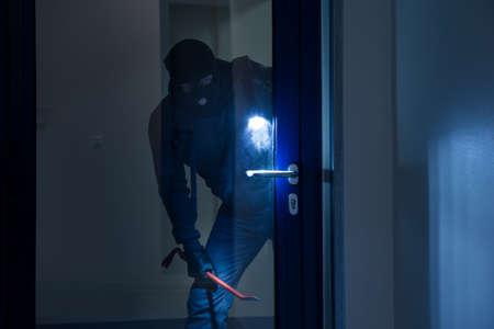 Dieb mit Taschenlampe versuchen, Glastür mit Brecheisen brechen