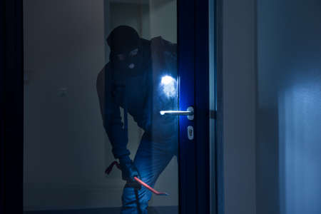 Thief with flashlight trying to break glass door with crowbar Stockfoto