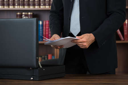 Midsection of male lawyer keeping documents in briefcase at table in office