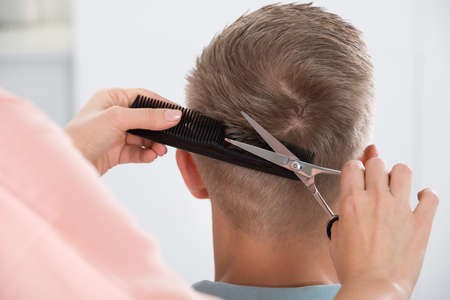 haircut: Rear view of young man getting haircut from female hairdresser at salon