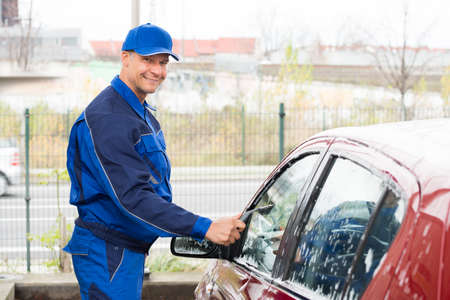 serviceman: Mature serviceman cleaning car window with wiper at service station