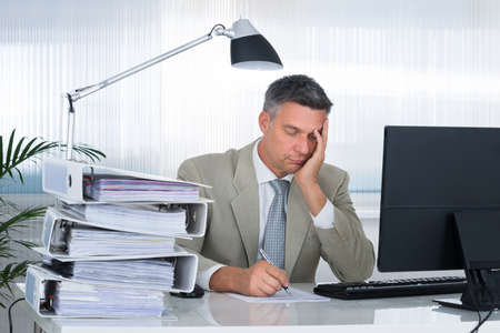 hands on head: Tired businessman with hand on face writing on document in office