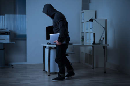 thievery: Full length side view of robber stealing laptop from office at night
