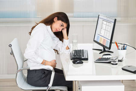 tense: Upset pregnant woman sitting at computer desk in office Stock Photo
