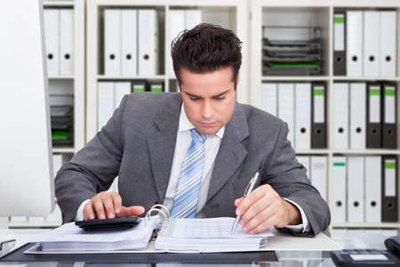 hombre escribiendo: Contador masculino joven cálculo de facturas en el escritorio en la oficina