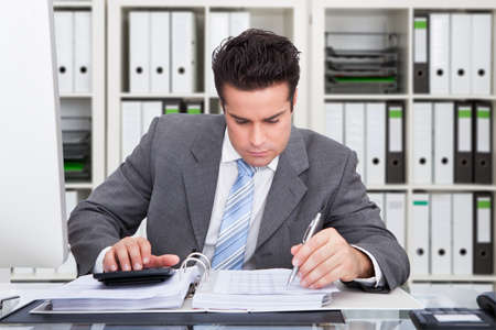 account executive: Young male accountant calculating bills at desk in office Stock Photo