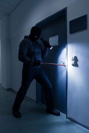 crowbar: Full length of thief with flashlight trying to break office door with crowbar