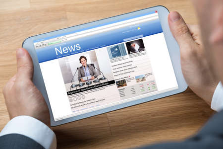 reading news: Cropped image of businessman reading news on digital tablet at office desk Stock Photo