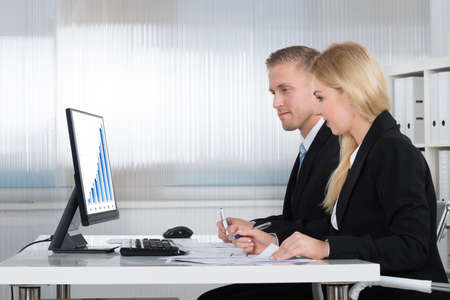 business marketing: Young businessman and businesswoman analyzing graph on computer screen at desk in office
