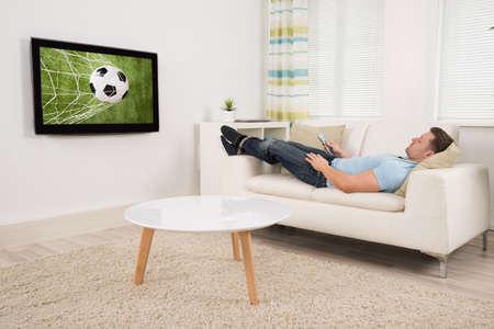 Relaxed medio volwassen man liggend op de bank tijdens het kijken naar voetbalwedstrijd op televisie thuis