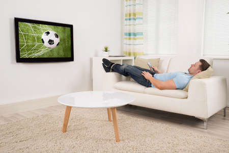 Relaxed mid adult man lying on sofa while watching football match on television at home