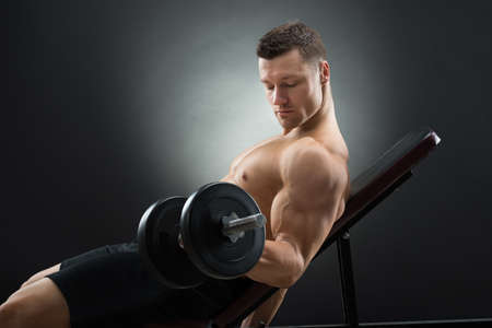 reclining chair: Side view of determined man exercising with dumbbells while reclining on chair against black background Stock Photo