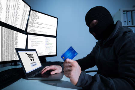 stealing money: Man wearing balaclava and holding credit card while using laptop at desk Stock Photo