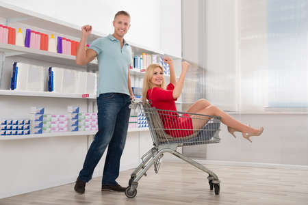 woman shopping cart: Portrait of happy man cheering with woman sitting in shopping cart at supermarket Stock Photo