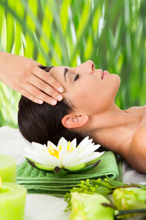 Side view of relaxed young woman receiving head massage at spa Stock Photo