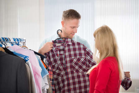 checked shirt: Young man showing checked shirt to woman in store