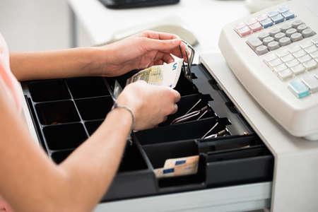 Duży kąt widzenia kobiet kasjera szukając zmian w szufladzie kasy w supermarkecie