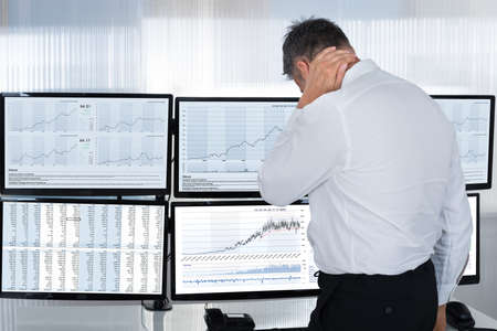 multiple: Rear view of stock market broker suffering from neck pain by multiple screens in office Stock Photo