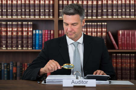 auditor: Mature male auditor scrutinizing financial documents at table in office Stock Photo