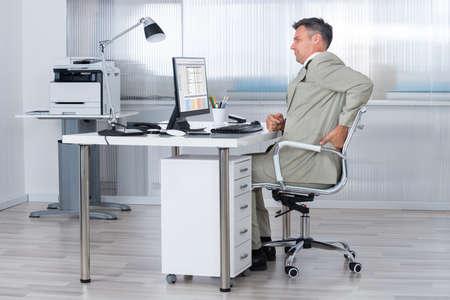 사무실에서 책상에 허리 통증으로 고통 회계사의 측면보기 스톡 콘텐츠