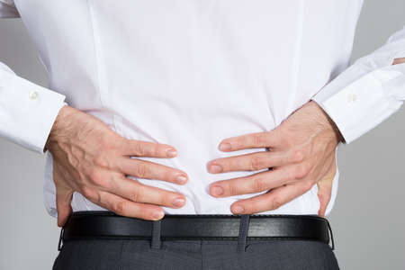 back injury: Rear view of businessman suffering from back ache against white background