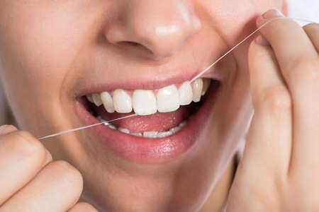 flossing: Closeup of young woman flossing teeth at home Stock Photo