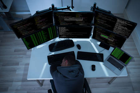 hood: High angle view of tired hacker sleeping near computers at night
