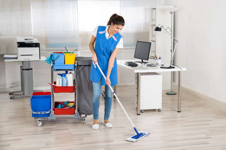 office uniform: Full length portrait of happy female janitor mopping floor in office