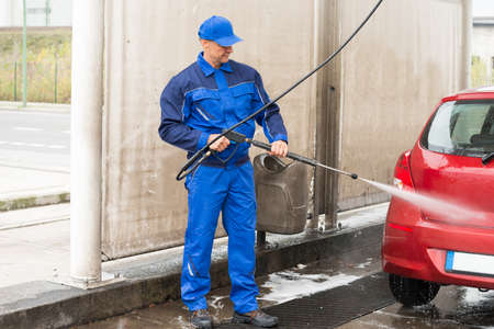 serviceman: Mature serviceman with high pressure water jet washing red car at service station