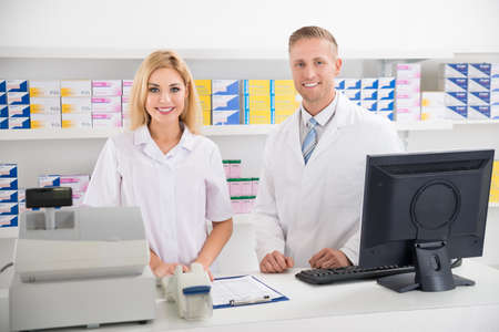 pharmacy: Portrait of male and female pharmacists smiling at counter in pharmacy