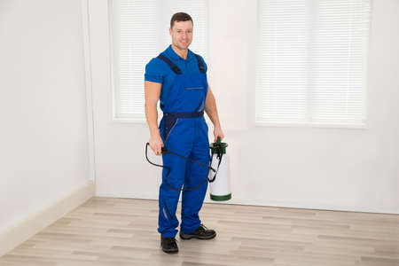 Full length portrait of smiling male worker holding pesticide container at home