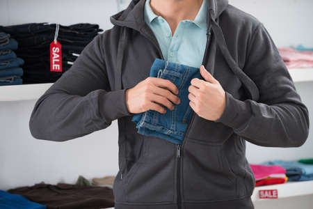 Midsection of man hiding jeans in jacket at store