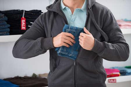 Mittelteil des Mannes versteckt Jeans in der Jacke im Shop
