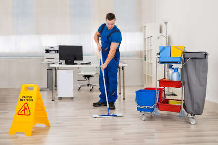 Full length of male janitor mopping floor in office 版權商用圖片