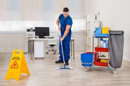 In voller Länge von männlichen Pförtner Säuberungs Boden im Büro