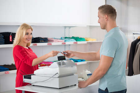 saleswoman: Beautiful saleswoman receiving payment from male customer in store Stock Photo