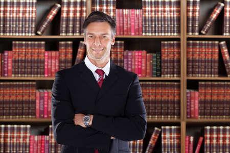 Portret van vertrouwen volwassen advocaat staande armen gekruist tegen boekenplank in kantoor