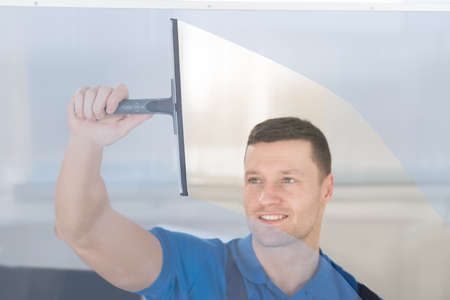 squeegee: Smiling mid adult worker cleaning glass window with squeegee