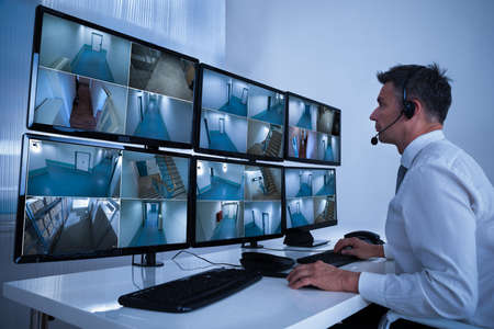 security room: Rear view of security system operator looking at CCTV footage at desk in office Stock Photo