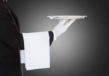 Midsection of waiter with napkin holding empty silver tray over gray background Stock Photo