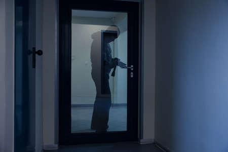 Full length of burglar using crowbar to open glass door at night