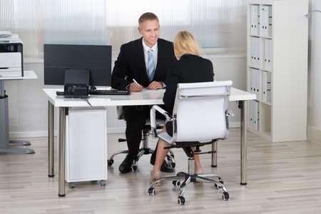 persona sentada: Joven empresario con candidata durante la entrevista en la oficina