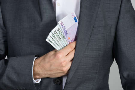 fraudulent: Midsection of businessman putting bribe in suit pocket at office Stock Photo