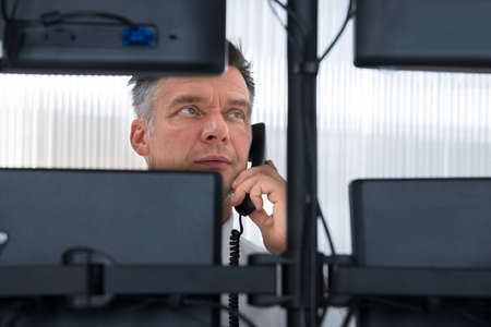 trading stocks: Mature male stock trader using telephone while looking at multiple computer screens at office