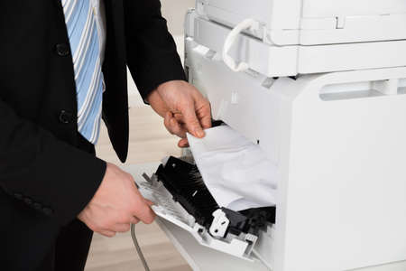 hand jam: Cropped image of businessman removing paper stuck in printer at office Stock Photo